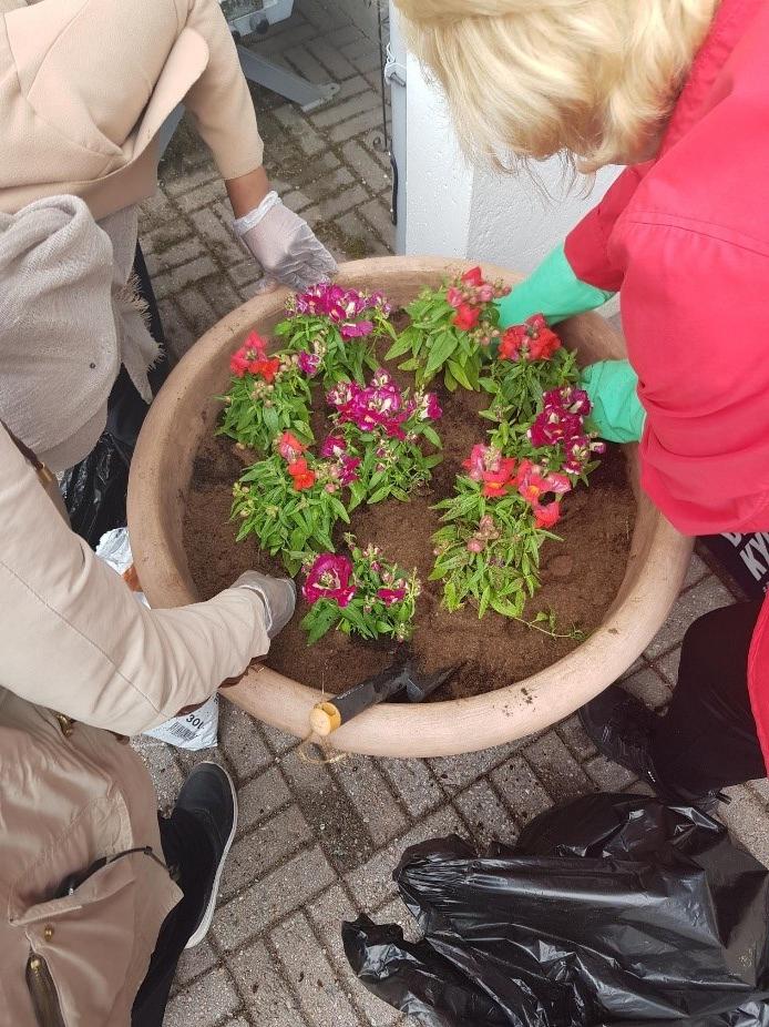 Nuoret ja asukas istuttamassa kukkia