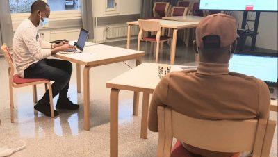 Kaksi nuorta miestä istuvat selin kuvaajaan, kumpikin oman pöydän äärellä ja maskit kasvoilla. Molemmat nuoret kirjoittavat kannettavalla tietokoneella.