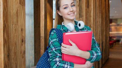 Nuori nainen hymyilee ja katsoo suoraan kameraan. Hänellä on selässä reppu, kädessä kansio ja kaulalla kuulokkeet.