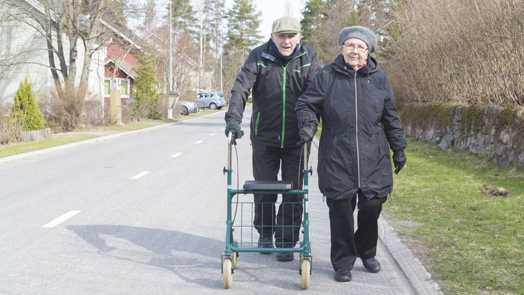 """""""Vanha mies ja vanha nainen kävelevät pientaloalueen tiellä kohti kameraa."""""""