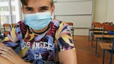 Nuori mies istuu tyhjässä koululuokassa kasvomaski päässään. Hän katsoo suoraan kameraan ja nojaa käsillään pulpettiin.