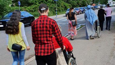 Joukko nuoria kävelee kadulla, selin kameraan. Kaksi heistä työntää ikäihmistä pyörätuolilla, ja yksi on käsikynkäss kävelevän ikäihmisen kanssa.