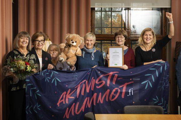 Kuvassa kuusi Aktivistimummoa kukkakimpun, nallen ja kunniakirjan sekä Aktivistimummot-banderollin kanssa.