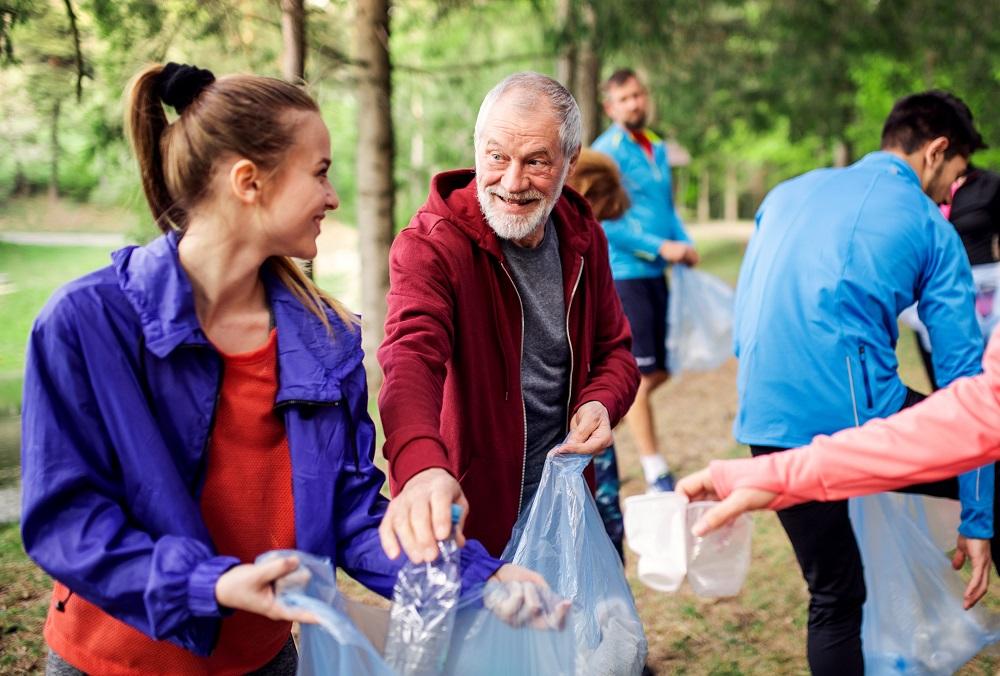 Kuvan etualalla vanha ja nuori henkilö katsovat toisiaan ja pitelevät pussia, jonne taustalla olevat keräävät roskia maasta.