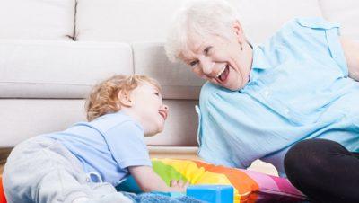 lapsenlapsi ja isoäiti leikkivät lattialla